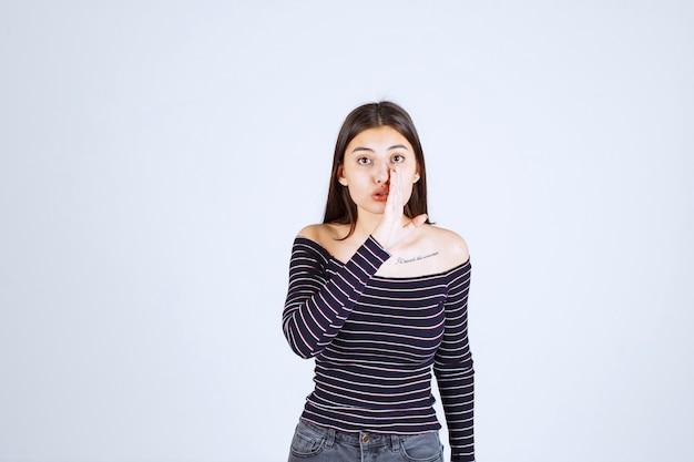 스트라이프 셔츠 듣기 또는 험담을하고있는 소녀.