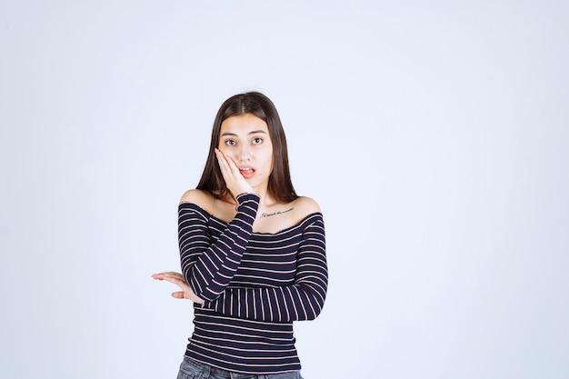 縞模様のシャツを着た女の子は混乱して興奮しているように見えます。