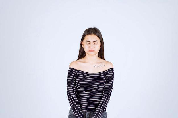 스트라이프 셔츠를 입은 소녀는 슬프고 실망 해 보입니다.