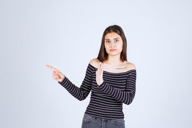 측면을 가리키는 스트라이프 셔츠에 소녀입니다.