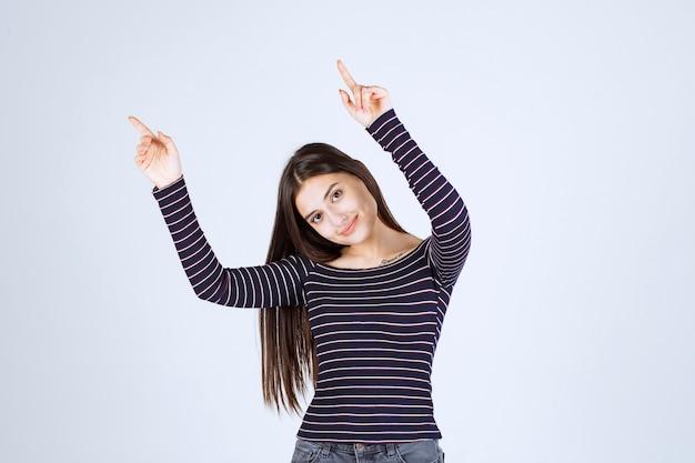 Девушка в полосатой рубашке, указывая вверх и показывая эмоции.