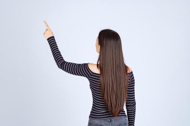 上向きに感情を示している縞模様のシャツの女の子。