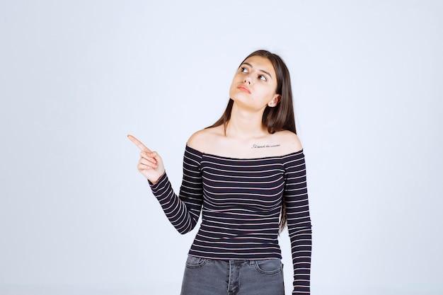 가리키는 및 감정을 보여주는 스트라이프 셔츠에 소녀.