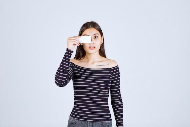 Девушка в полосатой рубашке, прикладывая визитную карточку к глазу.