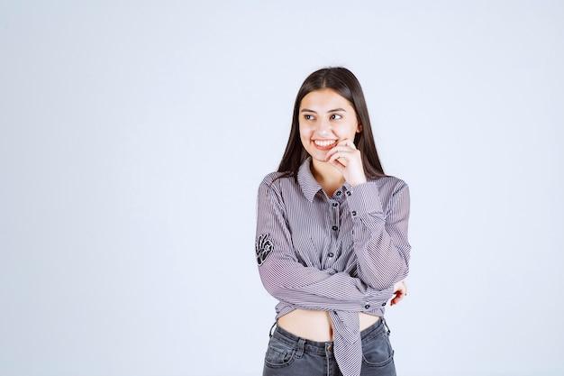 笑顔と幸せな気持ちの縞模様のシャツの女の子。