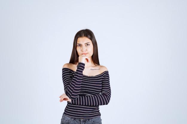 생각하고 분석하는 스트라이프 셔츠 소녀.