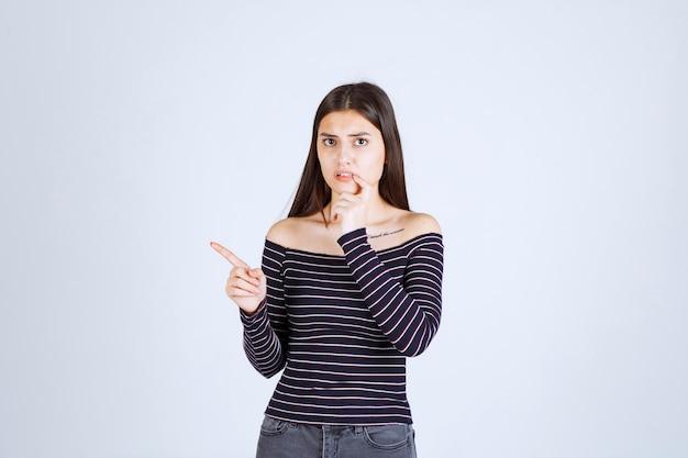 Девушка в полосатой рубашке думает и занимается мозговым штурмом.