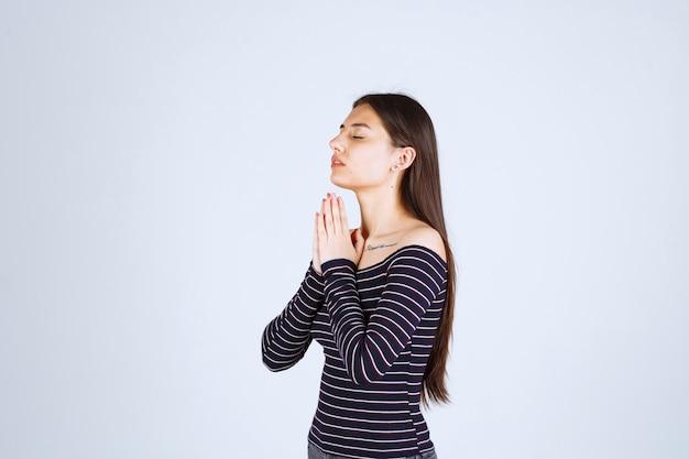 縞模様のシャツを着た女の子が両手を合わせて祈っています。