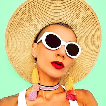 スタイリッシュなビーチアクセサリーの女の子。サングラス、イヤリング、帽子。ビーチファッションルック