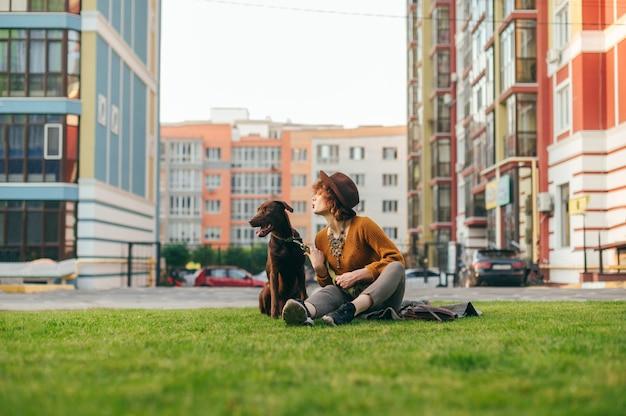 Девушка в стильной одежде и шляпе сидит на зеленой лужайке с собакой на поводке