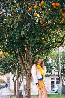 スタイリッシュな服を着た女の子がオレンジの木の幹にもたれかかっています。カメラを見てください。