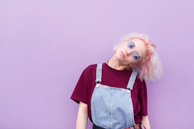 Девушка в стильной одежде розовых волос и солнцезащитные очки, которые лежат на фоне фиолетовой стены