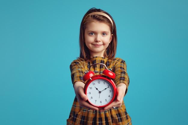 Девушка в стильном платье улыбается и демонстрирует будильник на синем фоне Premium Фотографии