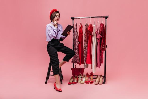 スタイリッシュな衣装と赤いベレー帽の女の子が椅子に座って、光沢のある服と靴でピンクの背景を思慮深く読んでいます。
