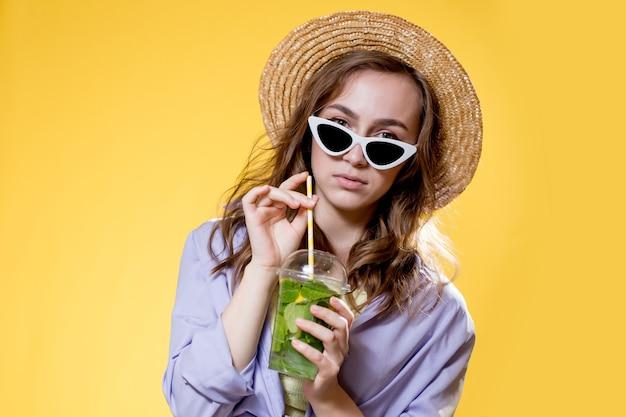 여름 옷을 입은 소녀는 흰색 트렌디한 선글라스를 쓰고 모히토 칵테일을 마시면서 즐기고 있습니다. 노란색 배경에 포즈.