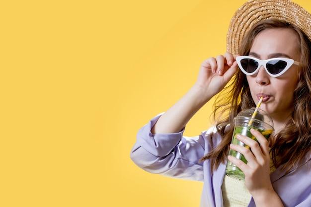 여름 옷을 입은 소녀는 흰색 트렌디한 선글라스를 착용하고 모히토 칵테일을 마시면서 즐기고 있습니다.