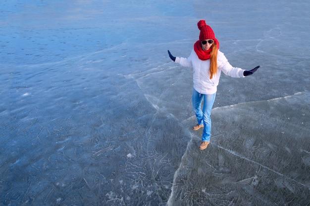 Девушка в солнцезащитных очках, белой куртке, красной шапочке и красном шарфе держит равновесие и веселится во время прогулки по льду по замерзшему озеру зимой