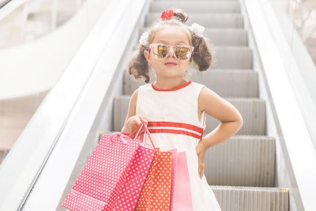 購入したモールのエスカレーターでサングラスをかけた女の子