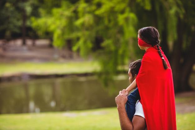 父親の肩に座っているスーパーヒーローの衣装の女の子