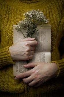 セーターの女の子は、マスタードカラーのロマンチックなコンセプトの女性の暖かいニットセーターの腕の中で本と花束の開いた紙の本と野生の花を保持しています