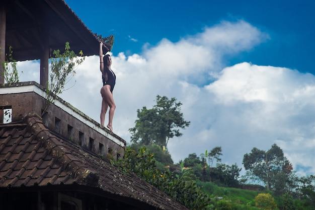 수영복 입은 소녀는 푸른 하늘과 함께 발리의 신비로운 버려진 썩은 호텔 지붕에 머물러 있습니다. 푸른 하늘