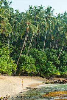 Девушка в купальнике гуляет по тропическому пляжу