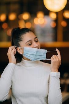 の女の子は彼女の保護医療フェイスマスクを脱ぐ