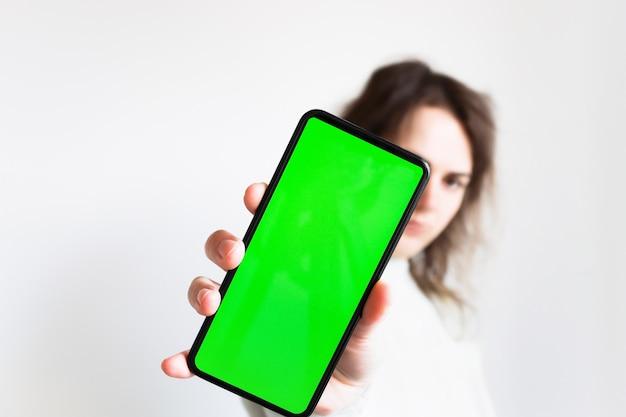 디포커스의 배경에 있는 소녀는 녹색 화면이 있는 뻗은 손에 스마트폰을 들고 있습니다