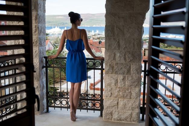 青いドレスを着た女の子がブラインドで戸口に立っています