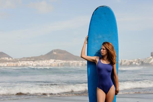 Девушка в синем купальнике стоит с доской для серфинга над атлантическим океаном