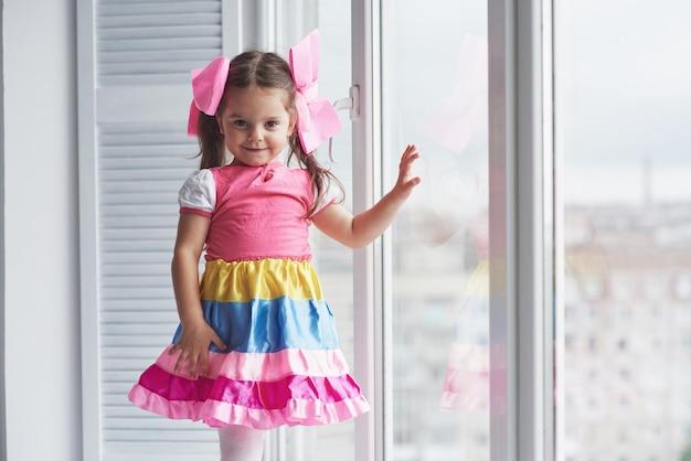 Девушка в ярком платье трогает оконное стекло