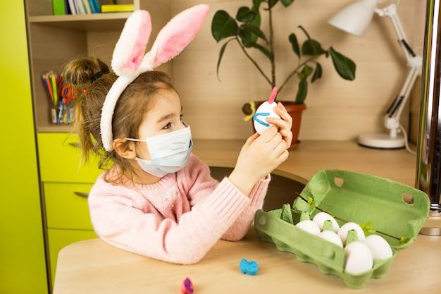 うさぎの耳の女の子は、卵と粘土から医療用マスクでイースターバニーを作ります。