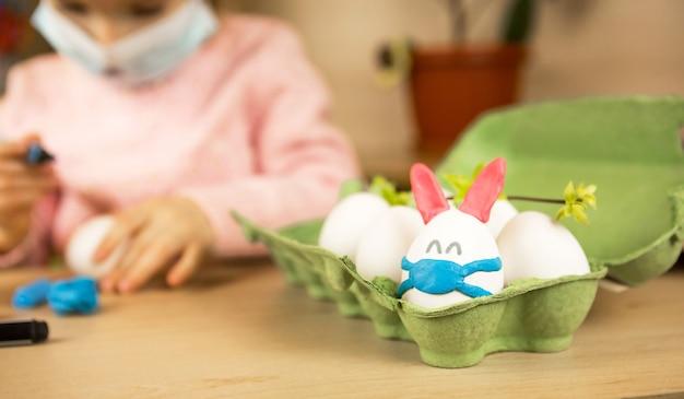 Девушка в ушах зайца лепит из яйца и пластилина пасхального кролика в медицинской маске.