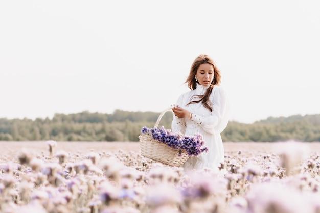 夏の自然の中でバスケットに花の花束を持つフィールドの女の子