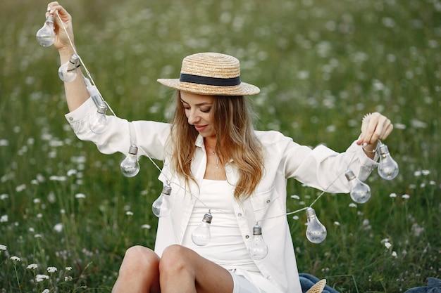 모자에있는 여자는 화환을 보유