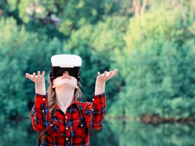 Девушка в шлеме виртуальной реальности на фоне природы. руки вверх. тонирование
