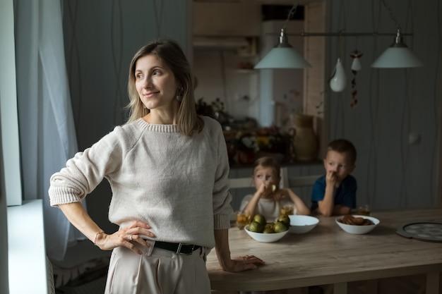 Девушка на кухне смотрит в сторону, на фоне мальчиков, сидящих за столом. фото высокого качества