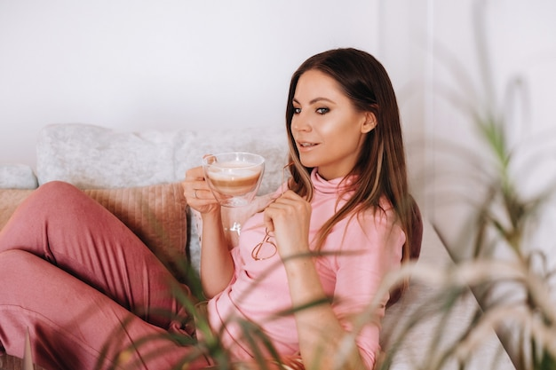 Девушка утром в пижаме дома пьет кофе