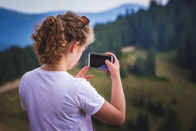 Девушка в горах снимает на мобильный телефон красоту окружающей среды