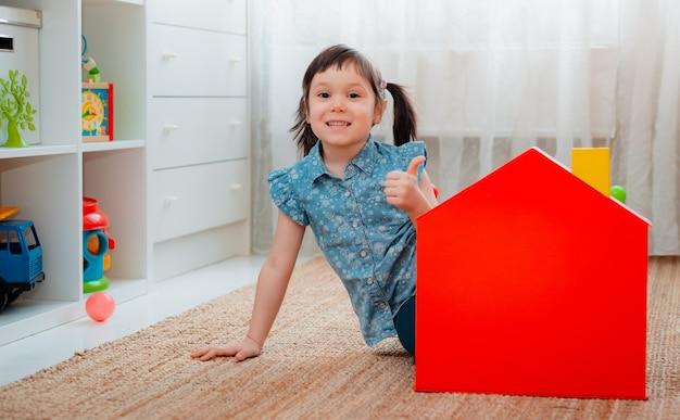 赤いおもちゃの家を持つ保育園の女の子