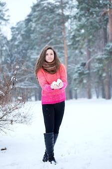 Девушка в парке счастлива играть со снегом
