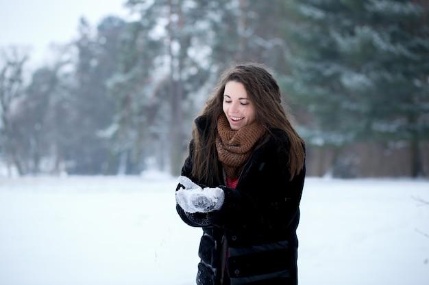 공원에서 소녀는 눈을 가지고 노는 행복