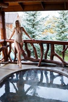 테라스에 뜨거운 물이 있는 수영장에 있는 소녀, 스파 바디 트리트먼트. 야외에서 휴식을 취하십시오. 웰빙. 스파 욕조가 있는 코티지. 야외 자쿠지. 여자와 자쿠지. 수영복을 입은 아름다운 모습의 여자