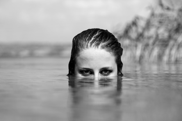 川の女の子。騒々しい白黒スタイルの写真。