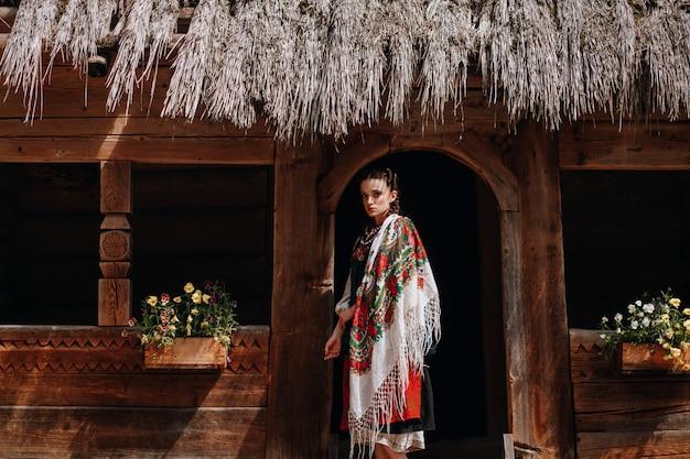 Девушка в украинском вышитом платье позирует возле дома