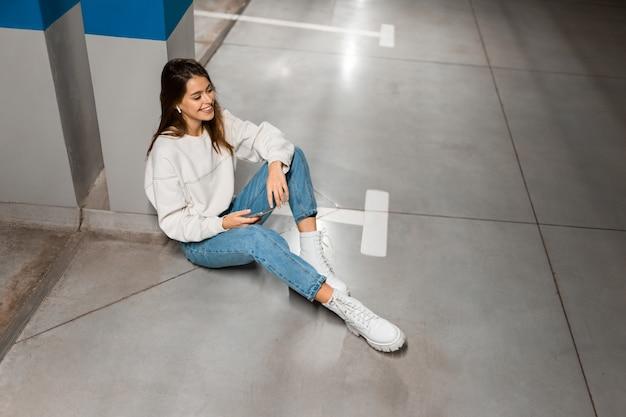 地下駐車場の女の子がワイヤレスヘッドホンで音楽を聴く