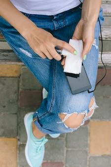 Девушка в рваных джинсах сидит на скамейке и чистит мобильный телефон антибактериальным спреем