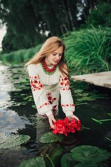 花の花輪を水に入れている伝統的なウクライナの服の女の子