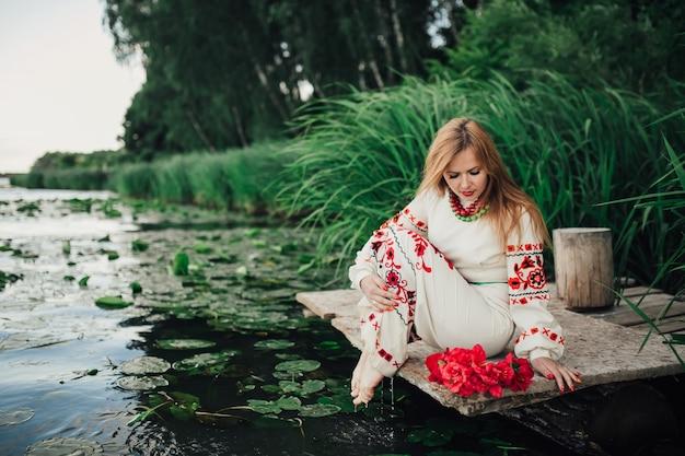 Девушка в традиционной украинской одежде, сидящей у воды