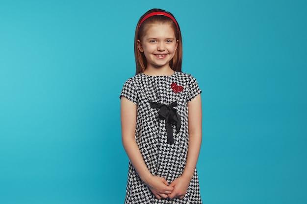 Девушка в модном платье, взявшись за руки и улыбаясь синей стене